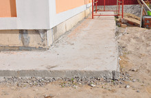 Close Up On House Foundation Waterproofing, Damp Proofing With Concrete Path To Avoid Water Leaks For House Wall.