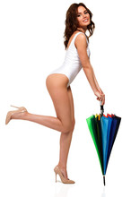 Pretty Girl In White Swimsuit Is Holding A Colorful Umbrella And Posing Against A White Background, Isolated