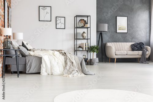 Spoed Foto op Canvas Hoogte schaal Black furniture, stylish sofa and a cozy double bed in a spacious, bright loft studio interior with orange brick wall and posters