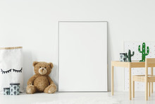 Mockup Poster, Teddy Bear And Material Basket Placed On The Floor In White Room Interior With Wooden Table And Small Chair. Paste Your Photo Here