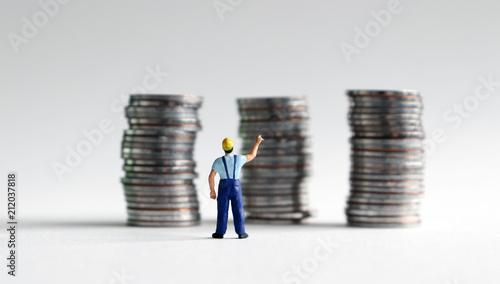 A miniature man reaching for a pile of three coins. Wallpaper Mural