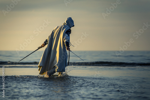 Photo Portrait of assassin in white costume with the sword at the sea