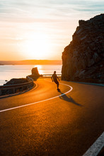 Young Man Skateboarding On Empty Street, Sea Sunset In Background
