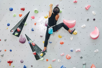Back view of woman on climbing wall with colorful artificial elements in bouldering center