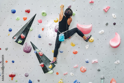 Back view of woman on climbing wall with colorful artificial elements in boulder Wallpaper Mural