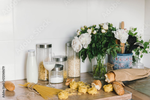 Fototapeta White tiles wall modern kitchen with chopping board,flowers,knifes,pasta,bread. White tiles wall modern kitchen with white top background and ingredients obraz na płótnie