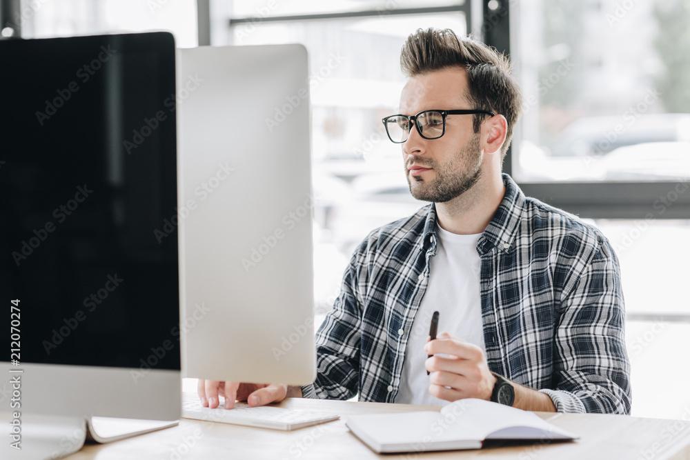 Fototapeta focused young man in eyeglasses working with desktop computer