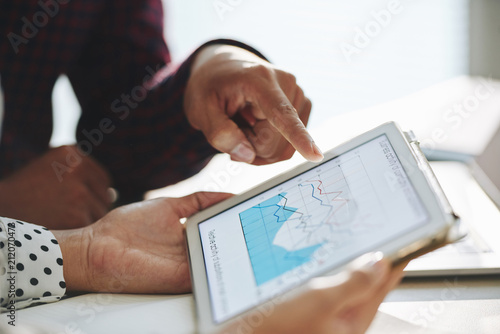 Obraz Close-up shot of crop man pointing at diagram on tablet screen while having discussion with colleague at workplace - fototapety do salonu