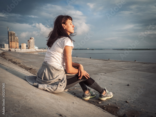 Photo Sports lifestyle: The girl is sitting on the city embankment