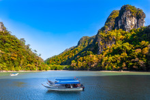 Magnificent Scenery Of The Kilim Geoforest Park In Langkawi, Malaysia. A Few Motorboats Are Moored In The Shaded Area Of The River And In The Background Are Mangrove Trees And Limestone Hills.