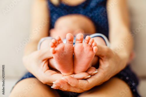 Obraz Mother holds little feet of newborn baby - fototapety do salonu