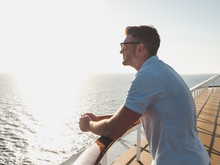 Stylish, Young Man In Sunglasses On The Deck Of A Cruise Ship, Looking Into The Distance Against The Background Of The Morning Sunrise And The Blue Sky. Concept Of Sea Travel And Recreation