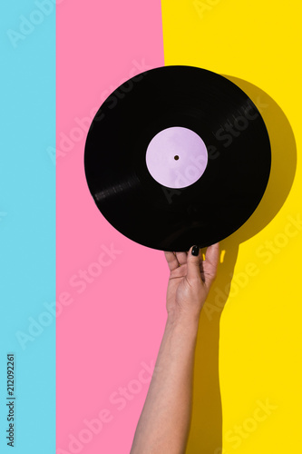 Female hand holding vinyl record over multicolored background  - 212092261