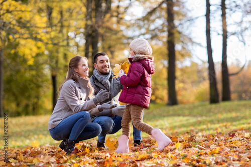 Spoed Foto op Canvas Hoogte schaal family, season and people concept - happy mother, father and little daughter with maple leaves at autumn park