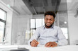 business and people concept - african american businessman with papers at office