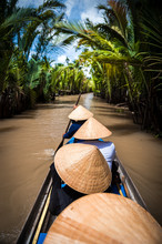 Rowing On A Traditional Boat With Traditional Hats On In A Canal On Mekong Delta In Vietnam.