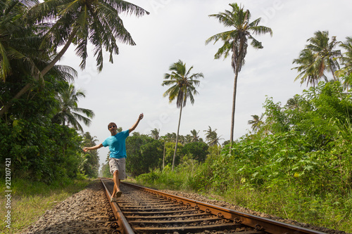 Fotografie, Obraz  Young man walking on railroad track while listening to music with headphones on his smartphone in rural area in Bentota, Sri Lanka