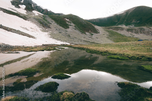 Foto op Aluminium Wit highlands lake landscape with water reflection, green hills and snow