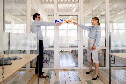 Fototapety, obrazy: Side view of young man and woman in formal outfits and sunglasses standing opposite each other and aiming toy guns while having fun in office