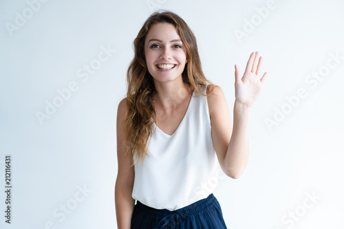 Fotografie, Obraz  Friendly pretty woman waving with hand and looking at camera