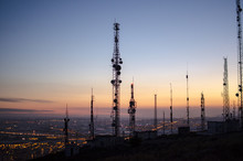 Communication Tower. Cell, Radio And Television Antennas On Top Of A Mountain And Below A Lit Coastal Village