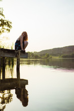 Sensual Young Woman Sitting On Pier