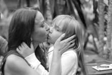 Gentle Kiss Of Mother And Little Daughter At A Family Party