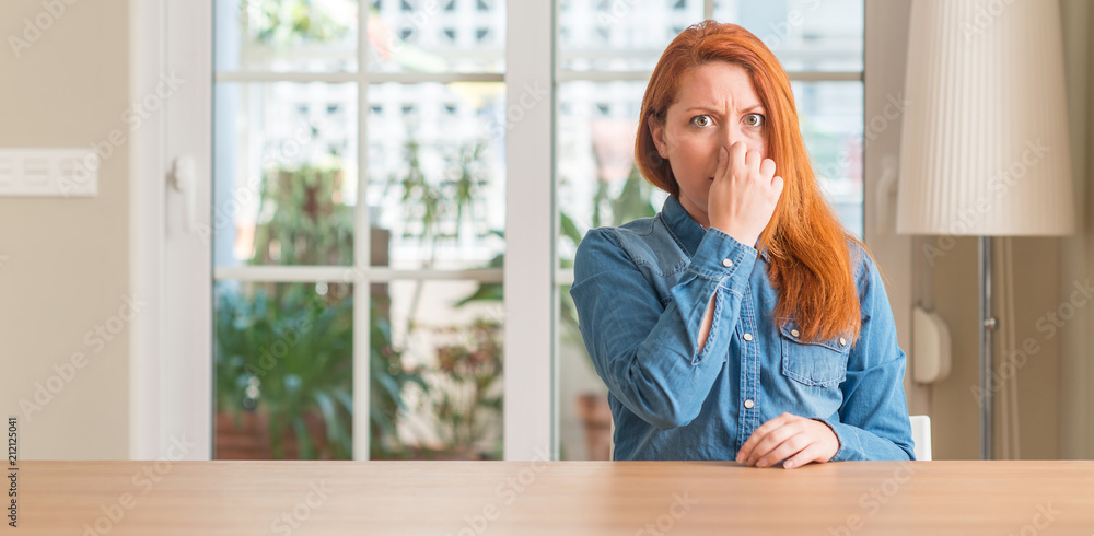 Fototapety, obrazy: Redhead woman at home smelling something stinky and disgusting, intolerable smell, holding breath with fingers on nose. Bad smells concept.