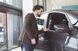 Handsome salesman examining car