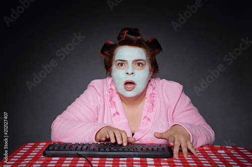 Fototapeta femme ronde et drôle avec bigoudis choquée par contenu ordinateur