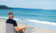 Senior man meditating on the beach
