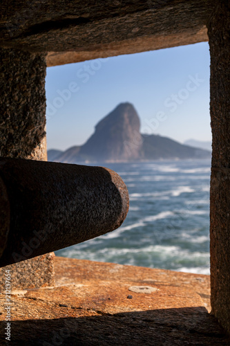 Old rusty canon sticking out of a fort in Niteroi with in the background across the bay the Sugarloaf mountain in Rio de Janeiro Fototapete