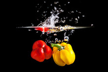 Yellow And Red Pepper Falling Into Water And Splashing Against Black Background