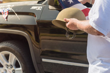 Close-up White Veteran Proudly Holding Military WWI Helmet (M1 Helmet) And US Flag During Parade. July 4th Or Veterans Day Poster Of WWII, Modern Wars. American Soldier Troop Background, Decorated Car