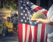 Vintage Tone A White Veteran Proudly Holding Military WWI Helmet (M1 Helmet) And US Flag. July 4th Or Veteran Day Poster Of WWII, Modern Wars. American Soldier Troop During Parade With People Watching