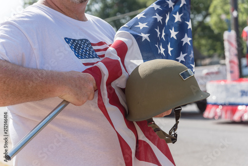 Photo  American veteran proudly holding military WWI helmet (M1 helmet) and US flag during parade