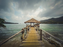 Wooden Pier With A Sheltered Hut On Ocean Coast On A Cloudy Day -