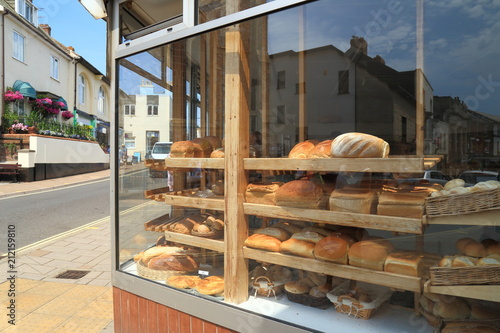 Shelves filled with freshly baked loaves of  bread diplayed in shop window in town of Sidmouth, East Devon