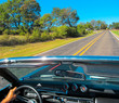 Open retro car riding along a Texas road. Sunny landscape with asphalt way, details of vintage transport, green trees and bright blue sky.