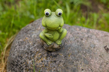 Decorative Frog In The Garden.ceramic Green Frog Figurine, Frog Sitting On The Stones.Copy Space