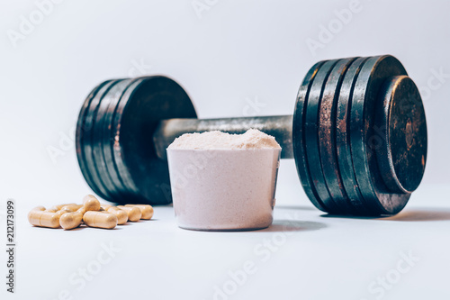 Whey protein powder in a scoop next to heap of vitamin pills Fototapeta
