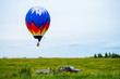 Bright colorful hot air balloon flying over field