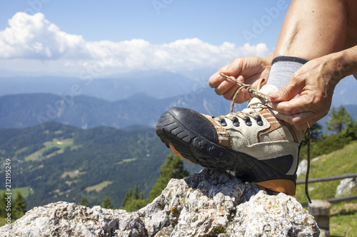 Fototapeta Hiker tying boot laces on rock, high in the mountains, space for text obraz