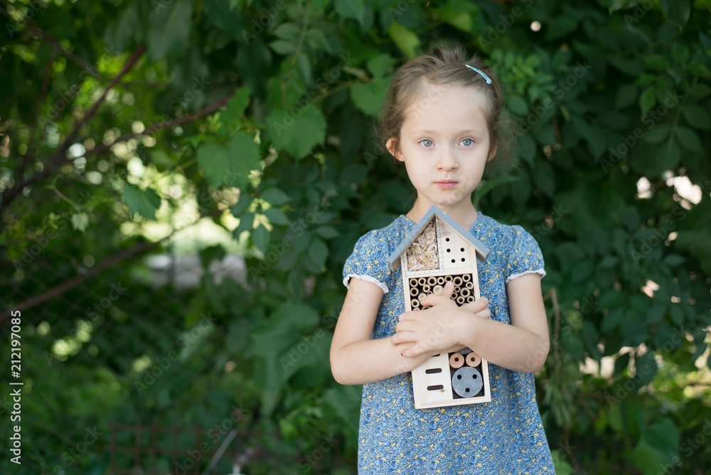 Fototapeta Green schooling. Girl holding insect hotel