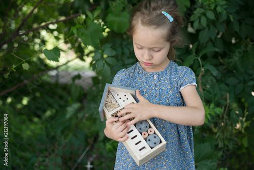 Obraz na płótnie Green schooling. Girl holding insect hotel