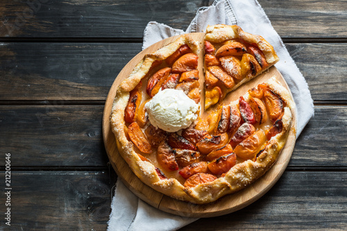 Fotografia Homemade apricot galette made with fresh organic apricotes on wooden table, top view