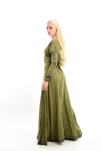 Full Length Portrait Of Blonde Girl Wearing Green Medieval Gown, Standing Pose Facing Away From Camera. Isolated On White Studio Background.