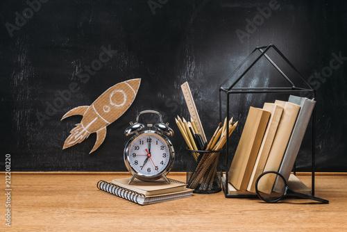 Fotografia  close up view of cardboard rocket on blackboard, pencils, clock, notebook and bo