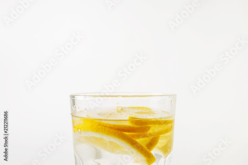 Photo Refreshing water with lemon in a glass on a white background on a hot day