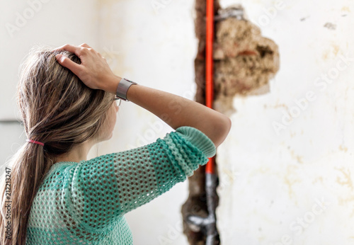 Fotomural  Woman looking at damage after a water pipe leak